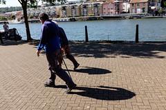Bristol; August 2016 (Daniel Durrans) Tags: oldman spikeisland street water stick oldlady harbourside boy oldwoman shadows man urban woman walking bristol streetphotography cane oldage dock shadow outdoors lady