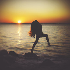 To Rise at the Setting (Shelby Robinson) Tags: ocean blue sunset red sea portrait orange beach girl silhouette yellow self canon hair rebel 1 rocks waves purple 4 ripples mm 50 teenage t1i
