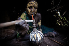 Surma tribe woman with her face painted while smoke from the typical pipe (anthony pappone photography) Tags: africa travel portrait woman black art face digital canon pose painting photography facepainting eyes paint artist faces image expression retrato african painted smoke pipe picture culture unesco clay tribes afrika omovalley oldwoman fotografia ethiopia ritratto surma reportage photograher afrique faccia eastafrica phototravel suri facepainted etiopia etnic  etnico etiope etnia argilla  loweromovalley etnica etnologia afryka losnios etiopija  etiopien etipia kibish yellowclay africantribe  etiopi tulgit  lowervalleyomo womantribe