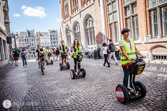 Tourists ride Segway on  streets of city center, Bruges, Belgium. (doctor.calavera) Tags: square hike bruges historic street shop center christmas holiday entertainment journey cafe gothic decoration grote wheel traditional transportation trip market flanders medieval walking restaurant landmark vintage markt brugge cityscape outdoor town new culture destinations flemish historical excursion city travel belgium leisure ages heritage tour tourism europe segway transport