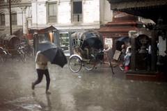 11-648 (ndpa / s. lundeen, archivist) Tags: street city nepal people man color building film rain umbrella 35mm buildings asian asia southeastasia rainyday candid nick citylife streetphotography streetlife 11 barefoot rainstorm kathmandu nepalese rickshaws 1970s rickshaw umbrellas raining 1972 katmandu himalayas sliceoflife nepali southasia dewolf cyclerickshaw nickdewolf photographbynickdewolf reel11