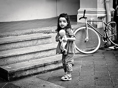 Cute Girl and Her Doll (ready_aim_snap) Tags: street people blackandwhite kid doll streetphotography cutekid girlwithdoll legacylens konicahexanon