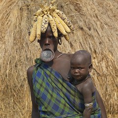 Mother Mursi Woman Wearing Corn Cob Headdress And Clay Plate Carrying Baby Ethiopia (Eric Lafforgue) Tags: africa people square mother picture plate tribal photograph blackpeople omovalley lip ethiopia tribe loincloth carrying corncob colorphoto headwear headandshoulders headgear nomadic eastafrica youngwomen headress lookingatcamera inarms womenwoman mursitribe indigenousculture snnpr southernethiopia truepeople 3539years exterioroutdoors liphanging omotic southernnationsnationalitiesandpeoplesregion blackethnicity ethiopianomovalley abyssiniahornofafrica mursimurzu dilatedextendeddilatedexpandedenlargedbroadenwiden inferiorlip liphole claydiscplatelipplatelipplugornamentjewelshandcr babytoddleryoungchildbabies claydiscplatelipplatelipplugornamentjewelshandcraftstraditionalpottery lfgethio3303