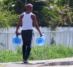 Water Bearer (Legin_2009) Tags: caribbean hommes guys outdoors person wifebeater hombres blackman outside  gente mec  personas persons homme man muscle  males black back mecs hombre  persona male street vest men blue mnner guy people  sandals