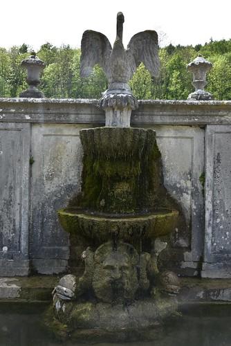 L'aigle en pierre et sa fontaine couverte de verdure