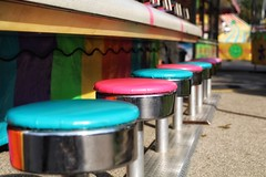 all in a row (s@ssyl@ssy) Tags: colour seats stools row fair carnival pink blue game colourful