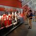 Members of the media touing the newly refurbished Reynolds Coliseum check out a display featuring Coach Norm Sloan's red plaid jacket and jerseys of National Championship players David Thompson and Lorenzo Charles.