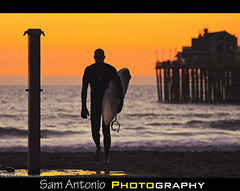 Rise of the Silver Surfer (Sam Antonio Photography) Tags: california sunset sea sky people orange usa cloud sun sunlight reflection beach nature wet water silhouette yellow horizontal standing walking outdoors photography pier sand holding surf sandiego dusk surfer watching fulllength wave surfing oceanside surfboard watersedge hobbies silversurfer vacations marvelcomics oneperson skill watersport oceansidepier tranquilscene californiabeach californialandscape traveldestinations colorimage leisureactivity gettingawayfromitall sandiegobeach oceansidebeach riseofthesilversurfer canoneos5dmarkii incidentalpeople samantonio samantoniophotography underthearm comicconsandiego2013
