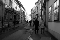 Sopron Street Scene (Adam Haranghy) Tags: street old people woman white man black streets architecture buildings walking photography blackwhite hungary fuji traditional architektur gebude sopron magyarorszg x100