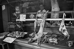 The Butcher (much0) Tags: bw italy blur reflection eyes market bn meat occhi butcher lamb sicily carne selling mercato catania sicilia riflesso macellaio agnello macchia vendita much0 darktable