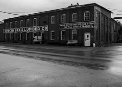 Duncan Box & Lumber Co (trainmann1) Tags: nikon d90 nikkor 18200mm amateur handheld huntington wv westvirginia south southern rain rainy bw blackwhite desaturated duncanboxlumber company graphic brick building street old historic classic antique outofbusiness millwork doors frames door forsale realty business