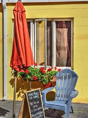 sit (albyn.davis) Tags: colors colorful vivid bright vibrant blue yellow orange umbrella window chair flowers sign