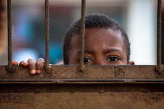 #30 Children Life. Your eyes behind a gate. You want to get away from school. Hell Ville Town | Madagascar (Daniele Romeo Ph) Tags: africa travel school portrait people students face kids portraits children kid shoes village child faces african think streetphotography portraiture thinking fisher madagascar fishers nationalgeographic travelphotography nosykomba travelphoto andriana hellville nosyiranja peoplefaces nosyb flickraward nikond3 nikonflickraward danieleromeo flickrunitedaward ampasindava flickrawardgallery flickrtravelaward nossib streettravelphotography andrianahanko ambatuzavavy lokobreserve antafianambitry