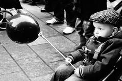 Not in the Mood (rainie_ho) Tags: uk boy people blackandwhite mono scotland kid toddler child serious glasgow balloon streetphotography cap pram greyscale rainieho