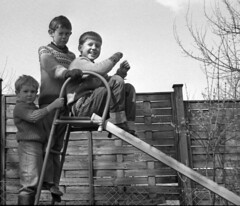 On the slide - Fun in play clothes (theirhistory) Tags: boy shirt fence garden child jeans jumper wellies plimsols platmslide