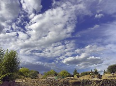 a fence (Amiti) Tags: fence wall stone brick border sky cloud blue white green tree leaves granadilla extremadura cceres spain espaa outdoors daylight summer old antique village olympus