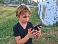 Intense Pokemon Go player (Pejasar) Tags: game iphone pokemongo park norman oklahoma boy concentrate intense child grandson