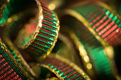 A Wee Bit of Red - HMM! [Explored] (SauceyJack) Tags: christmas winter red holiday macro green wrapping gold holidays shiny colorful december bokeh flash twist explore present ribbon coil twisted 2012 coiled macrolicious explored macromondays 10028l canon1dx aweebitofred sauceyjack