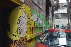 frowning down the alley (mcfcrandall) Tags: streetart cars lane alley mural woman blond yellowhair frowning painted parked narrow confined