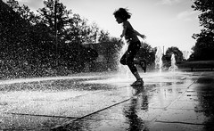 Splash (marcin baran) Tags: splash water fountain wet drops run running girl kid child hand play playfull street streetphotography urban city candid candidphotography pov perspective light afternoon sun sunny reflection gliwice poland polska fuji fujifilm x100 x100t trees marcinbaran black white blackandwhite mono