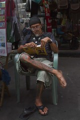 business is slow (Magne M) Tags: street man norway tattoo reading glasses book warm bangkok sandals candid character streetshot thaland