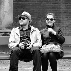 Bench people (Akbar Simonse) Tags: street camera people urban bw holland blancoynegro netherlands monochrome hat sunglasses canon bench bag beard couple zwartwit candid nederland streetphotography bank tourists bn busted clocked streetshot stel straatfotografie straatfoto dedoka akbarsimonse
