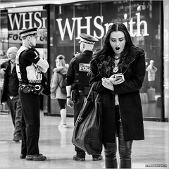 Contagious (John Riper) Tags: johnriper street photography straatfotografie square bw black white zwartwit mono monochrome candid john riper canon 6d 24105 l liverpool england uk people waiting limestreet limestreetstation woman yawn yawning infectious contagious whsmith ringing phone bored bobby glass reflection