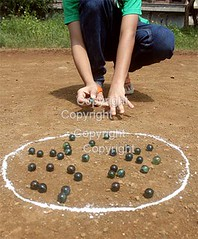 Kid Playing Marbles (picsrover) Tags: people india playing green childhood playground vertical closeup outdoors photography sand child indian young multicoloured competition jeans soil leisure marbles strategy variation oneperson aiming partof humanhand colourimage differentialfocus 1213years humanbodypart leisuregame takingashotsport childrenonlywristwatchtshirt