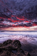 Fire in the Skies (waltmanNZ) Tags: ocean sunset red newzealand seascape beach clouds landscape photography sand rocks waves auckland p westcoast hitech waterscape sigma1020mm 10mm cokin ndfilter kariotahi canon60d