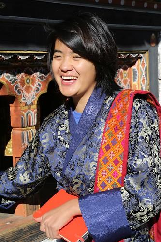 Bhutanese student Pema beams a smile as she turns a prayer wheel (Thimphu, Bhutan)