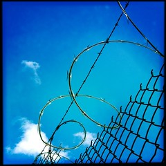 Razor ribbon sky (Harmie V) Tags: blue sky clouds fence security chainlink barbedwire razorwire razorribbon bridgeportharbor johnslens hipstamatic standardflash sugarfilm