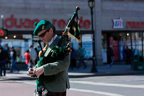 Traditional Bagpiper with Cellphone near Duane Reade Convenience Store