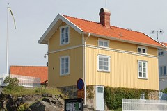 Coastal house (K Nilsen) Tags: houses homes windows summer orange house yellow facade fence coast wooden sweden flag cottage vine roofs coastal tiles sverige flagpole bohusln tiledroof grundsund summerhome skaft summerhomes
