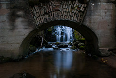 An Old Mill (modestmoze) Tags: vilnius lithuania 2016 500px outside outdoors water waterfall reflection shadows white black brown grey concrete constructions architecture green blue moss grass nature naturephotograph arch wet rocks under sand park day river one mill old bricks