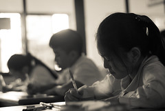 Working hard? ;) (Angelo G.I.O.) Tags: life morning school girls portrait people bw sun sunlight white black english students monochrome kids pen pencil portraits sunrise children table thailand 50mm lights daylight morninglight blackwhite chair nikon focus asia dof classroom bokeh availablelight bangkok working culture teacher indoors daytime teaching mystudents nikkor 18 sunrays responsible naturalight schoolwork thaipeople sunglare morningglow thaiculture morningtime thailady bokehlicious creamtone d3000 bangkae nikond3000 totallythailand beyondbokeh phetkasemroad phetkasem group62 phetkasem69 maneewattana englishplanet