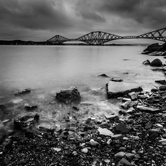 Moody Bridge (Wan ~stuck in catch up loop) Tags: longexposure water scotland rocks dusk stones squareformat southqueensferry forthrailbridge sigma1020mmdchsm nikond7000 wmekwiphotography mekwicom