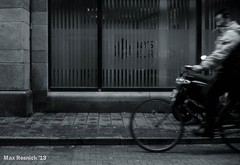 Rid'n (Max Resnick) Tags: vacation blackandwhite motion blur film netherlands amsterdam bike bicycle analog movement europe candid streetphotography rangefinder sidewalk riding scala agfascala200 leciam6 autaut canon50mm14ltm