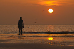 Watching the day away (Explored) (Phil Orr Photography) Tags: sunset sculpture men beach silhouette iron place another crosby