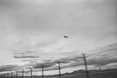 LAS (Colton Davie) Tags: canoneoselan7 airplane roadtrip bw nevada 35mm film 2014 march lasvegas ilforddelta100 fence sky airport iso100 xtol las motionblur