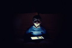 Small boy in the dark holding a tablet (Nasos Zovoilis) Tags: life city blue boy sleeping portrait brown white playing reflection cute love home apple beautiful face childhood closeup dark fun toy happy kid bed eyes hands toddler europe alone child play hand looking little sweet head expression room small joy young mother adorable handsome son athens read greece sofa health blond attractive worry inside charming care tablet hold ipad