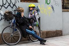 Every Breath You Take (lothar1908) Tags: street italy muro strada italia gente candid milano 100mm jeans mamma bici telefono borsa casco coppia bicicletta esterno bambino scritte cestino mwpotw seggiolino 5dmarkiii