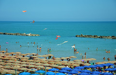 Summer days (angelsgermain) Tags: beach sun sky sea summer swimmers bathers umbrellas kites breakwaters people crowded heat pesaro marche italia italy adriaticsea