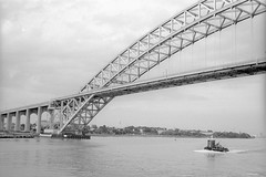 Tugboat, Bayonne Bridge (Alexander Rabb) Tags: bridge film blackwhite newjersey nikon kodak nj infrastructure tugboat nikonf bayonne newyorkharbor kodaktrix400 bayonnebridge killvankull workingharbor seriesezoom3672mmf35 hiddenharbortour workingharborcommittee maritimecommerce seriesezoom36~72mmf35