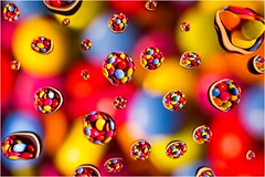 Raining Smarties (beninfreo) Tags: 18 australia 50mm 5d3 kenko canon psychedelia candy sweet smartie colour abstract refraction reflection droplet drop water macro