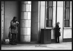 Two worlds apart (snapforu.com) Tags: street bw woman magazine beard eyes phone candid coat text homeless exhale inhale bigissue cigarettesmoke mygearandme