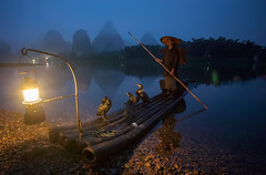 Setting Off (TheFella) Tags: china morning travel blue light portrait mountain man mountains slr water lamp hat digital photoshop sunrise canon river cormorants person eos dawn liriver li boat photo fishing fisherman asia guilin yangshuo working chinese pole hills photograph figure processing lone 5d mystical worker cormorant bluehour dslr fareast lijiang southchina mkii guangxi markii eastasia  postprocessing travelphotography ricehat lijiangriver  cormorantfisherman cooliehat  thefella paddyhat 5dmarkii  conormacneill thefellaphotography
