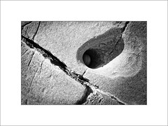 Ground Down - A Round Pebble in an Elliptical Hole. (Mikec77) Tags: bw sedimentaryrocks pebble trapped