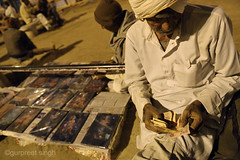 selling Gods... (gurpreet_singh.) Tags: street india man money night nikon god photos goddess oldman images roadside krishna seller mohan sangam allahabad earnings d4 prayag earning kumbh triveni 2013 utterpradesh livliehood mahakumbh hundu