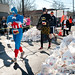 Superheroes check their race time as they pass the stack of completed doughnut boxes.