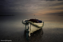 Take a bow. (Simon Rich Photography) Tags: uk winter sunset sea sky sun beach water clouds evening coast boat still fishing sand sailing post stones horizon rope calm east shore bow rowing parked groyne essex clacton defence anglia martello moored simonrich mrmonts simonrichphotography